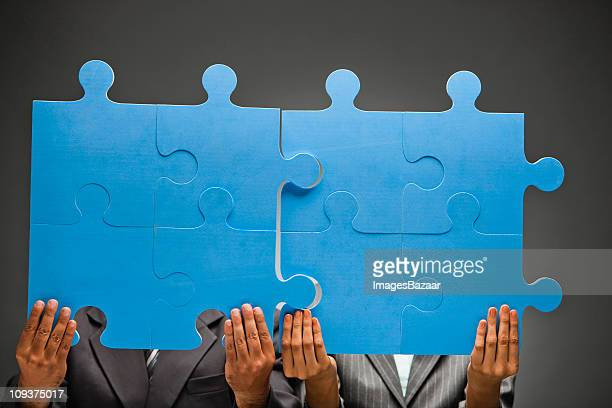 Two young businesspeople adjusting large blue jigsaw pieces