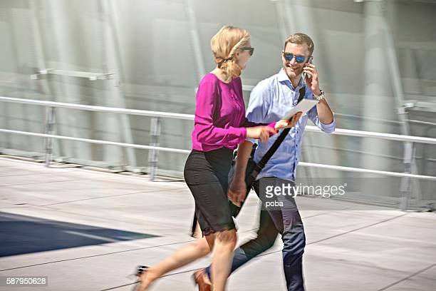 Two young businesspeople running late for a meeting