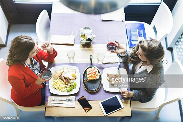 Two young businesswoman having a breakfast at restaurant and tal