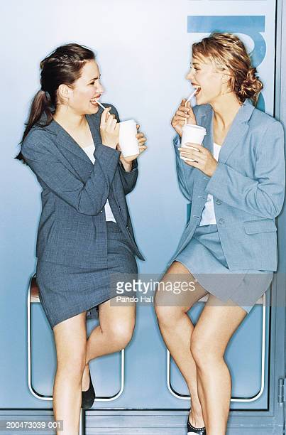 Two young businesswoman sitting on bar stools having drinks, smiling