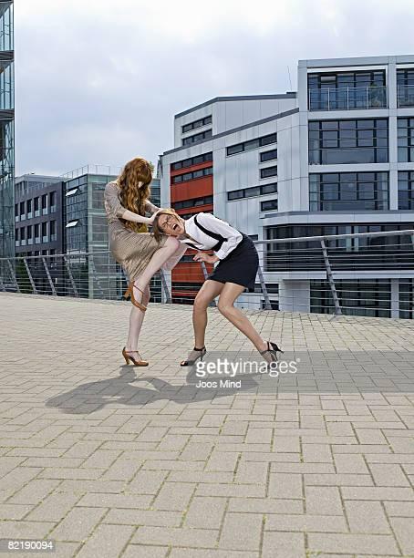 two young businesswomen fighting outdoors - kämpfen stock-fotos und bilder
