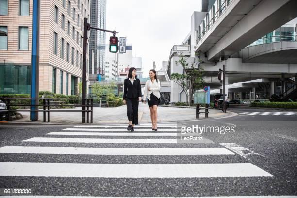 dois jovens empresárias em tóquio, japão - travessia de pedestres marca de rua - fotografias e filmes do acervo