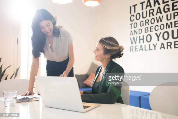 two young businesswomen meeting in creative office - heshphoto fotografías e imágenes de stock