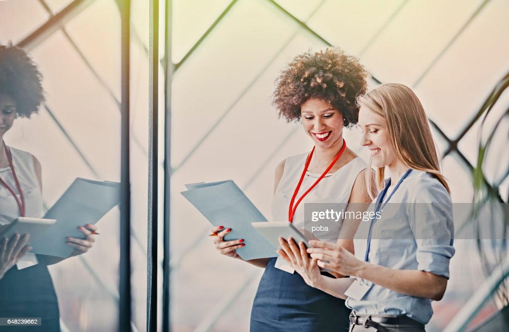 Two young businesswomen reading paperwork at meeting in conference room : Stock Photo