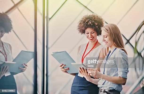 Twee jonge vrouwelijke ondernemers lezen papierwerk bij de vergadering in de vergaderzaal