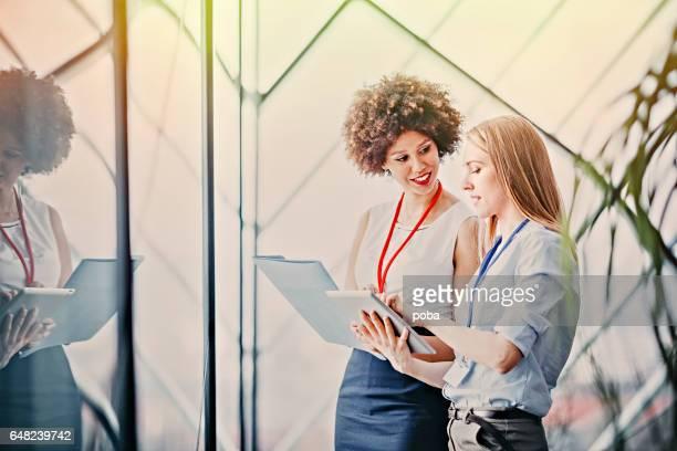 twee jonge vrouwelijke ondernemers lezen papierwerk bij de vergadering in de vergaderzaal - like button stockfoto's en -beelden
