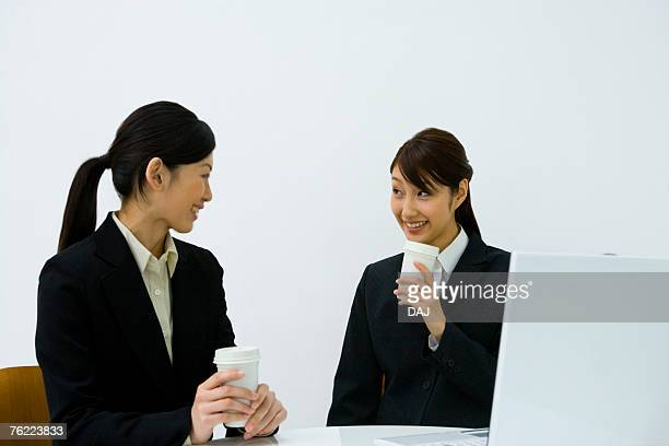 Two young businesswomen sitting at desk, smiling and holding paper cups, front view, side view, white background, Japan