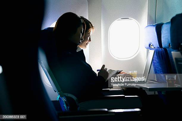 Two young businesswomen sitting in airplane, working on laptop