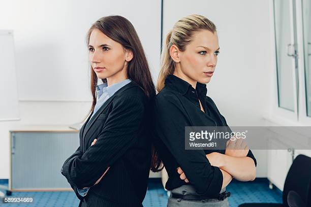 Two young businesswomen standing back to back