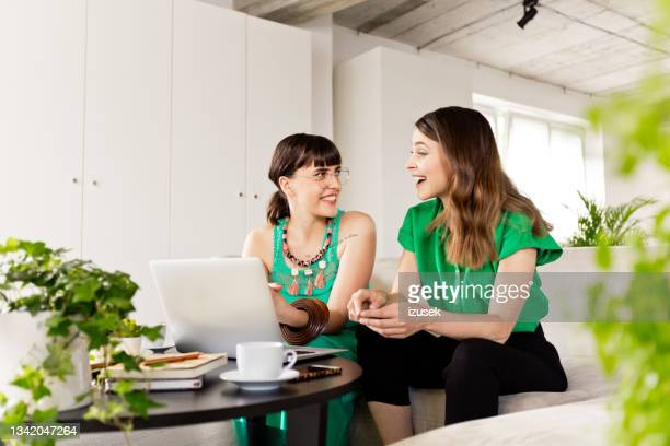 two young businesswomen working together - izusek stock pictures, royalty-free photos & images