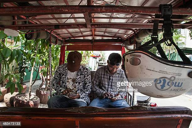 Two young Cambodian tuktuk drivers use their smartphones to check social media on April 9 2014 in Phnom Penh Cambodia Leaked to the media for the...