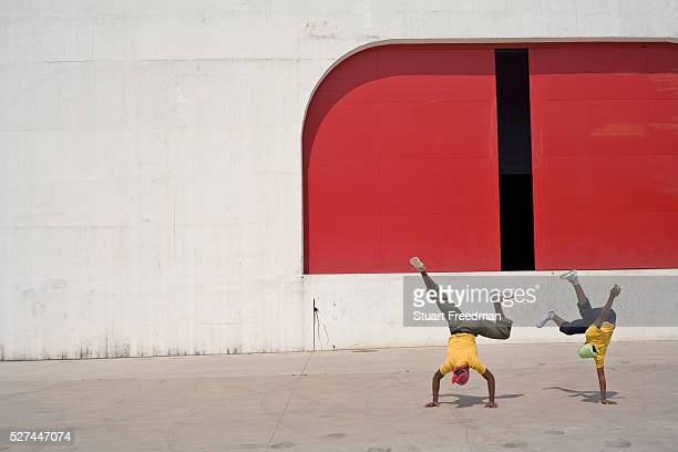 Two young Capoeiristas practice Capoeira outside a Modernist theatre designed by Oscar Niemeyer Capoeira is a mixture of martial arts games and dance...