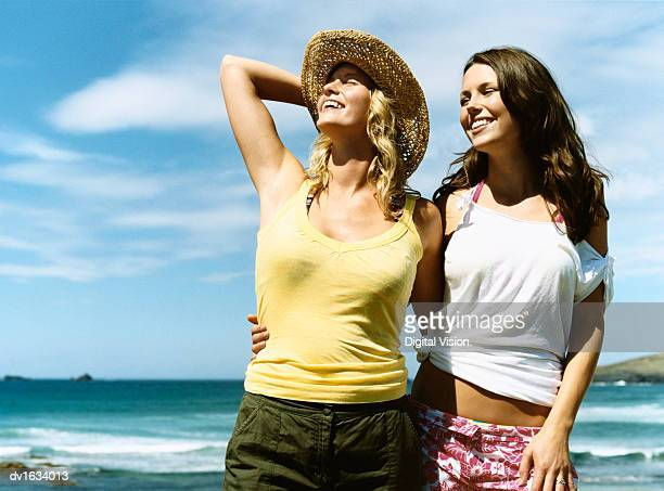 Two Young Carefree Women Stand Side by Side on the Beach With Their Arms Around Each Other