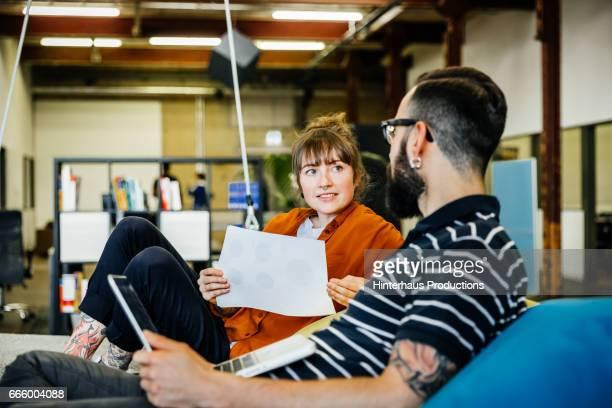 two young casual business people having an informal meeting - equipamento de lazer - fotografias e filmes do acervo