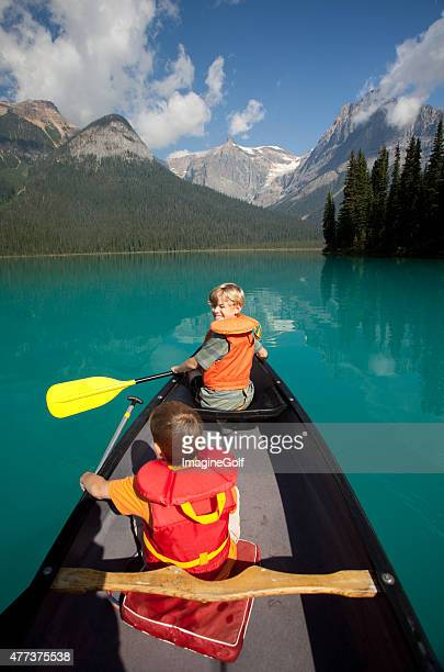 Two Young Caucasian Boys Paddling a Canoe in Canadian Rockies