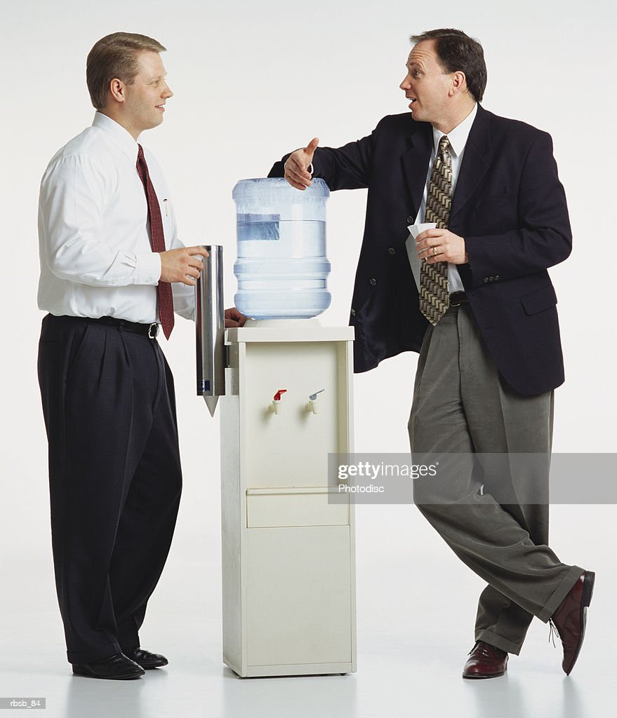 two young caucasian businessmen are standing around a watercooler conversing with eachother : Foto de stock
