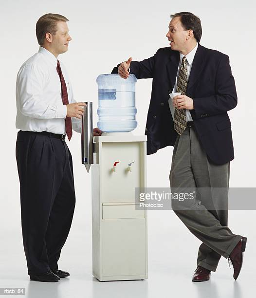 two young caucasian businessmen are standing around a watercooler conversing with eachother - water cooler stock pictures, royalty-free photos & images