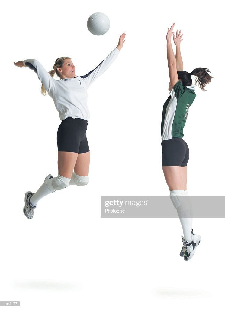 two young caucasian female volleyball players from opposing teams square off as one jumps and hits the ball while the other prepares to block : Foto de stock
