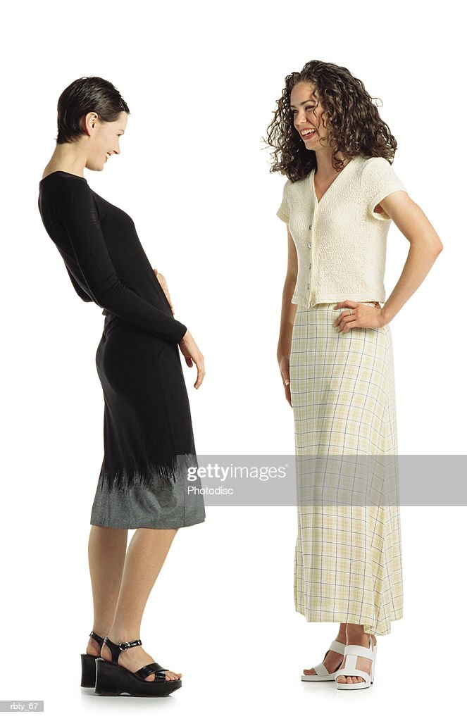 two young caucasian women wearing dresses stand together talking and laughing together : Foto de stock