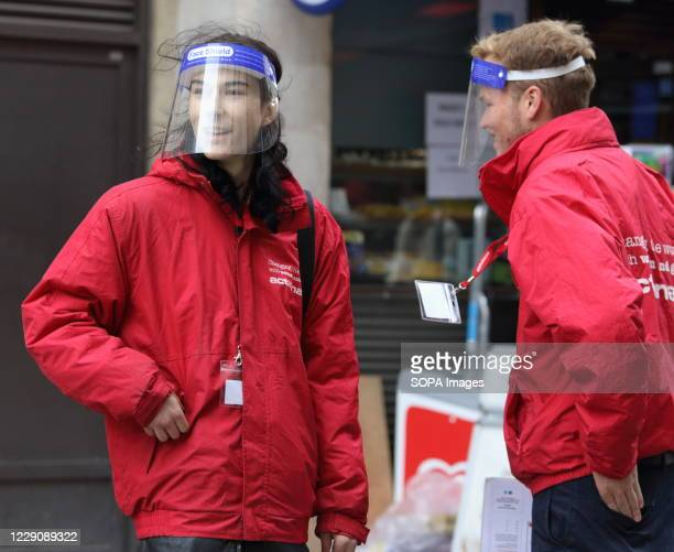 Two young charity collectors are seen wearing perspex face shields. Public people are seen wearing facemasks while out shopping in London following...