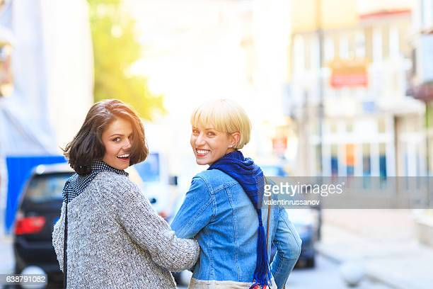 Two young cheerful friends walking on street