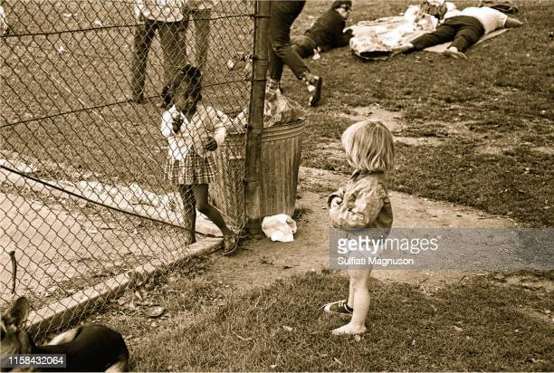 Two young children breech the racial divide as people nap on the grass, near a trash can at the 1st Elysian Park Love-In on March 26, 1967 in Los...