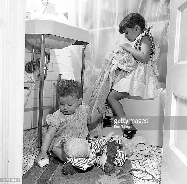 Two young children clean and wash items in the bathroom New York New York 1948