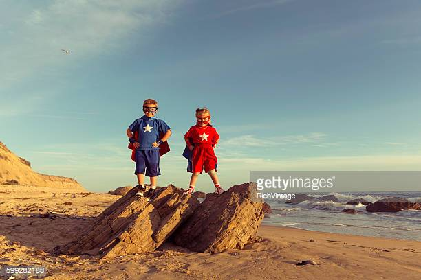 two young children dressed as superheroes stand on rock - superhero stock pictures, royalty-free photos & images