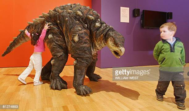 Two young children inspect Minmi a lifesized dinosaur puppet as it walks around an exhibition titled 'Hatching the Past Dinosaur Eggs Babies'...