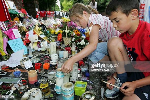 Two young children light candles among floral tributes at the scene where 18yearold Anthony Walker died by McGoldrick Park Huyton on August 5 2005 in...