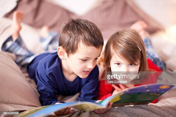 Two young children lying on bed looking at picture book