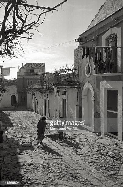 Two young children pulling a small cart along a street in the old town centre of San Giovanni Rotondo Italy