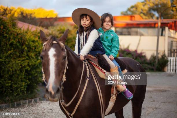 Two young children seen riding a horse during the Ciolla Week rodeo in Montevideo Every April since 1925 the Criolla Week Festival is celebrated in...