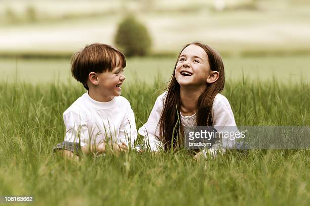 Two Young Children Sitting in Grass and Laughing