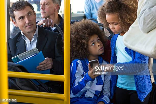 Two Young Children Using Smartphone on Bus