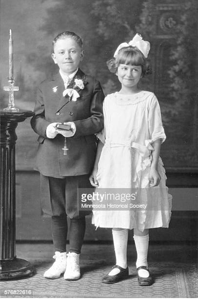 Two young children wearing their best church clothes pose for a portrait at their First Communion