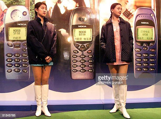 Two young Chinese women working for Nokia stand ready to help customers with questions they may have about the company's mobile phones at a shopping...