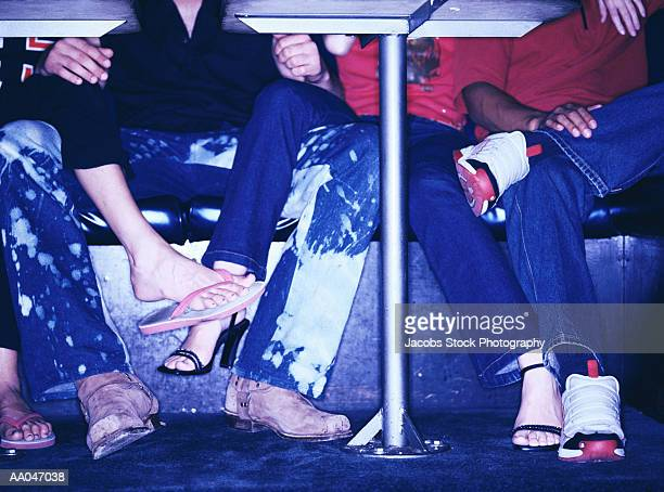 candid feet under table