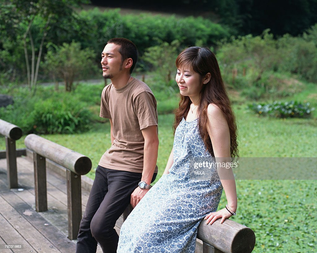 Two young couple sitting on wooden fence : Stock Photo