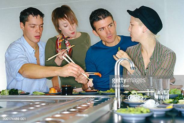 Two young couples eating at sushi bar