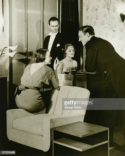 Two young couples gathered around piano in living room, (B&W)