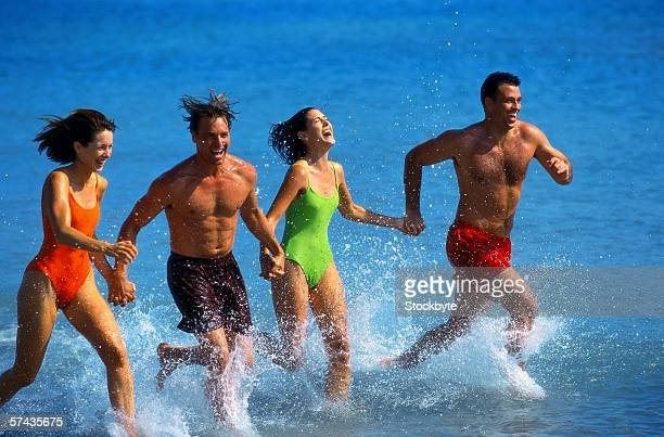 two young couples holding hands and running in the sea