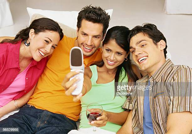 two young couples looking at mobile phones