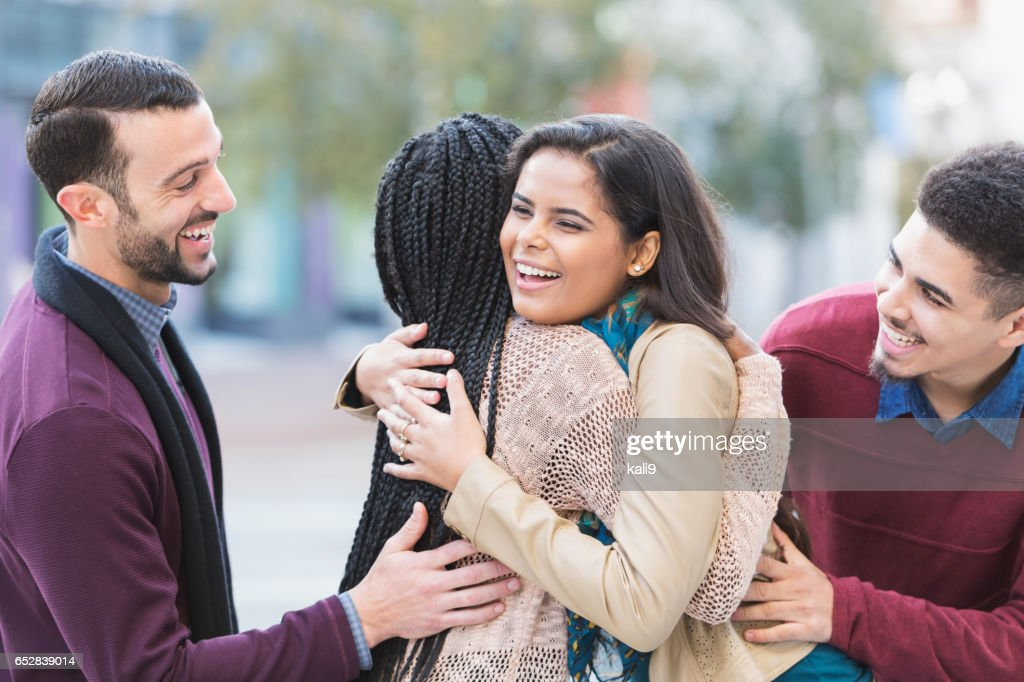 Two young couples meeting, greeting on city street : Stock Photo