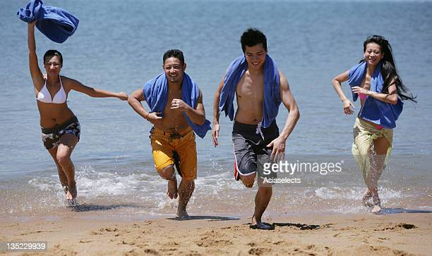 Two young couples running on the beach and smiling