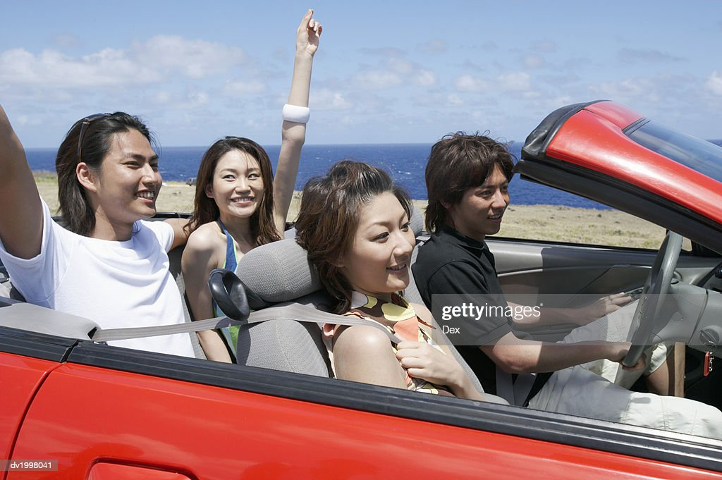 Two Young Couples Sit in a Convertible, Driving by the Sea : Stock Photo