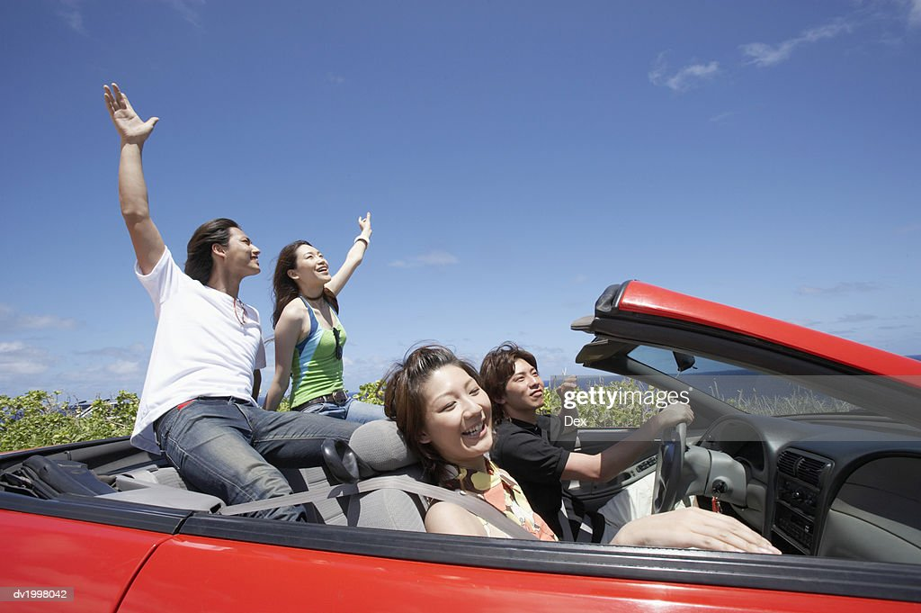 Two Young Couples Sit in a Convertible, One Couple With Their Arms in the Air : Stock Photo