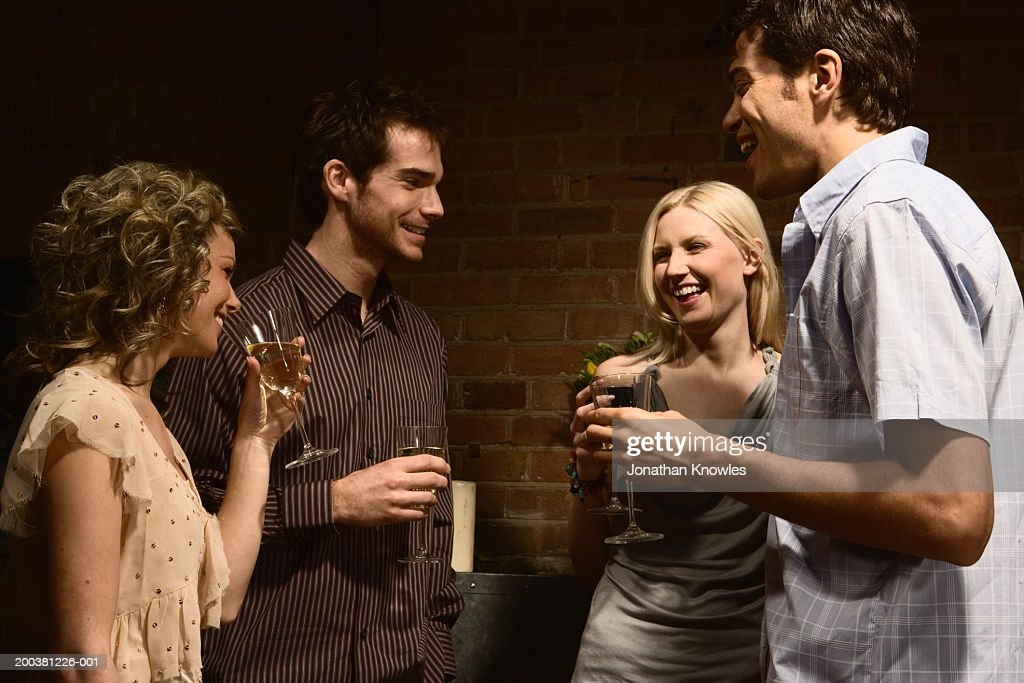 Two young couples socializing, holding drinks and laughing : Stock Photo