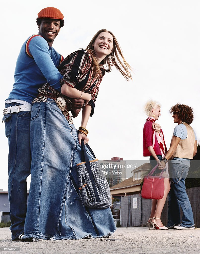 Two Young Couples Stand in an Urban Setting, Laughing and Talking : Stock Photo