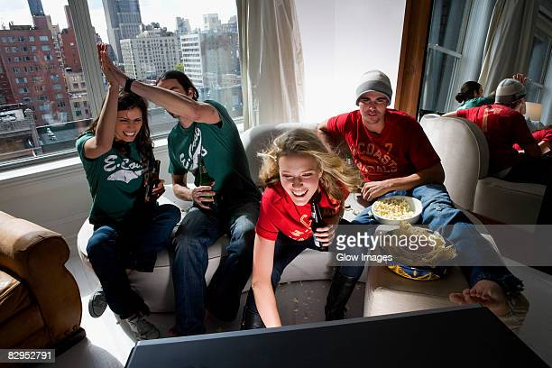 Two young couples watching television and drinking beer in a living room